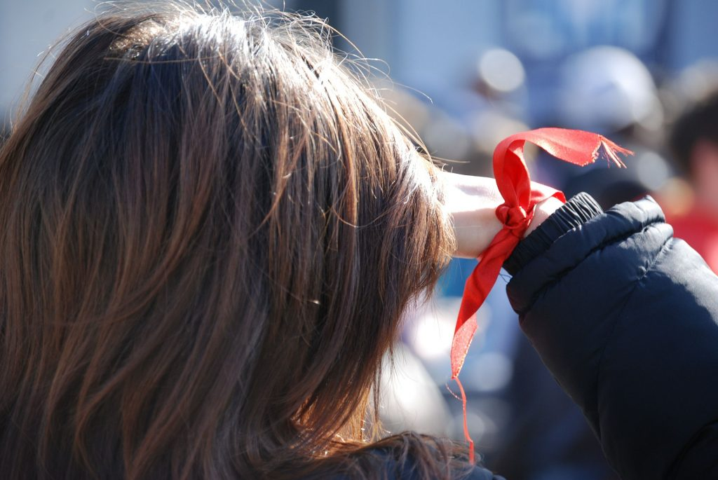 Woman Wearing Red Ribbon to Promote HIV AIDS | Breast Cancer Car Donations