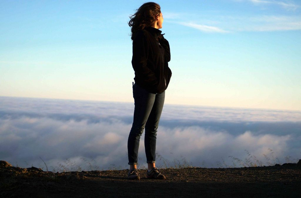 Woman Standing in Mountains with Clouds | Breast Cancer Car Donations