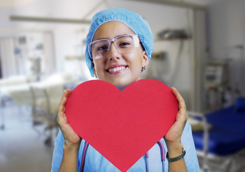 Nurse Holding a Heart Cardboard Sign | Breast Cancer Car Donations