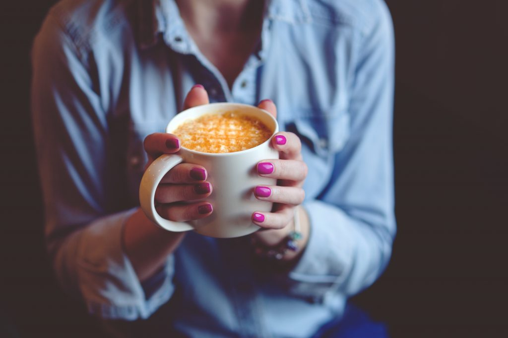 Woman Holding Cup of Latte | Breast Cancer Car Donations