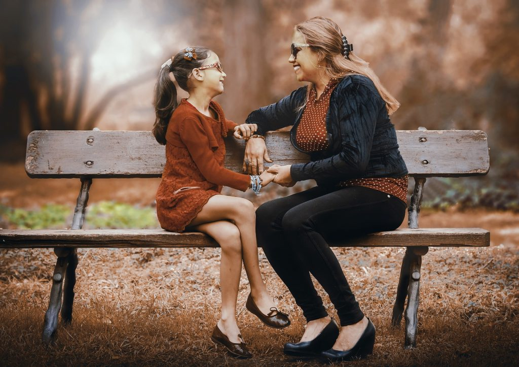 Mother And Daughter on a Bench Outdoors | Breast Cancer Car Donations