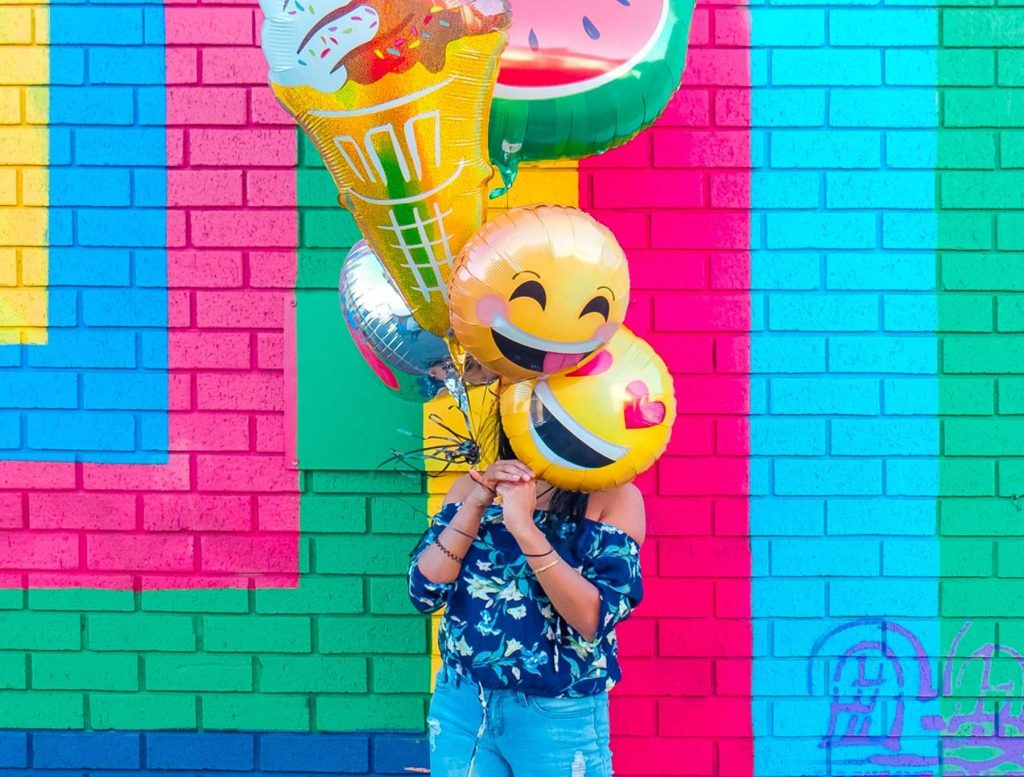 Person Holding Emoji Balloons | Breast Cancer Car Donations