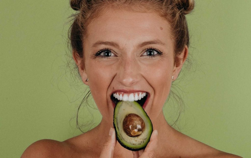 Person Holding a Slice of Avocado | Breast Cancer Car Donations