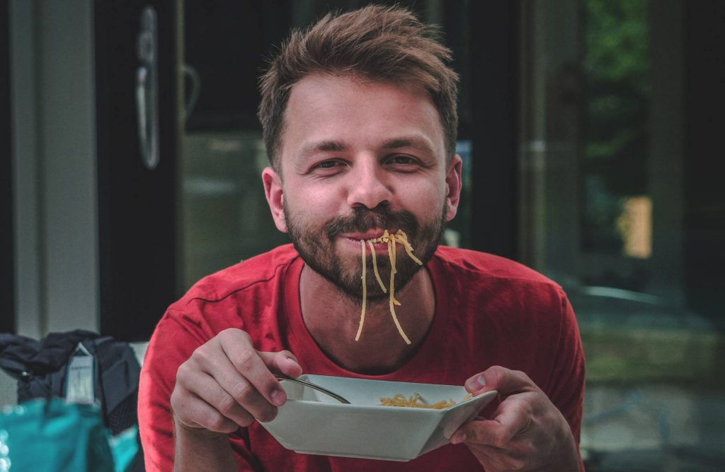 Person Enjoying a Bowl of Noodles | Breast Cancer Car Donations