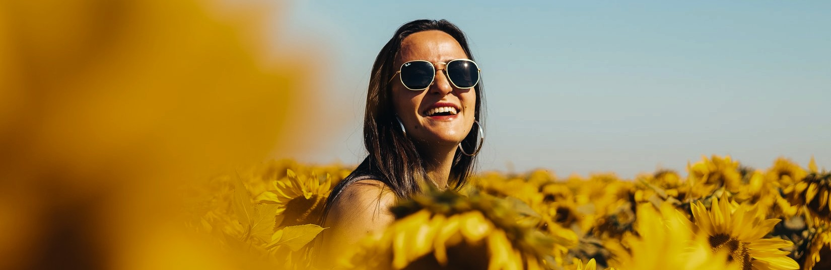 Person Smiling on a Sunflower Field | Breast Cancer Car Donations