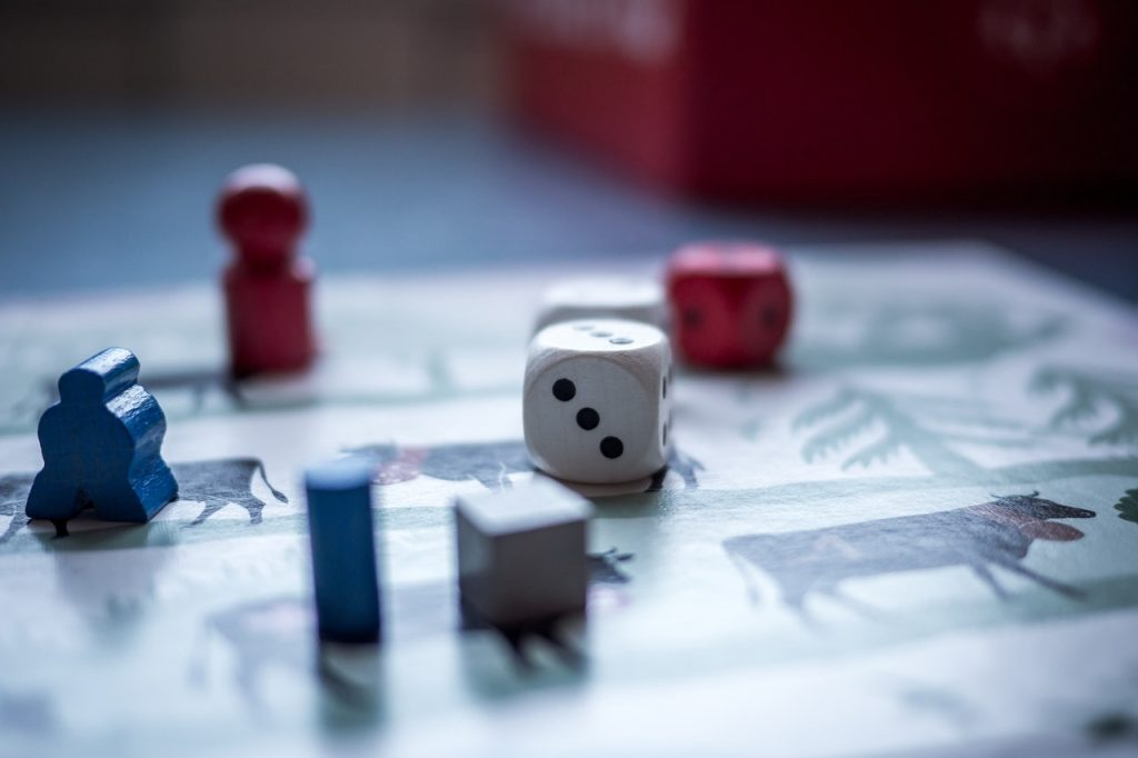 Dices and Wooden Pieces on Game Board | Breast Cancer Car Donations