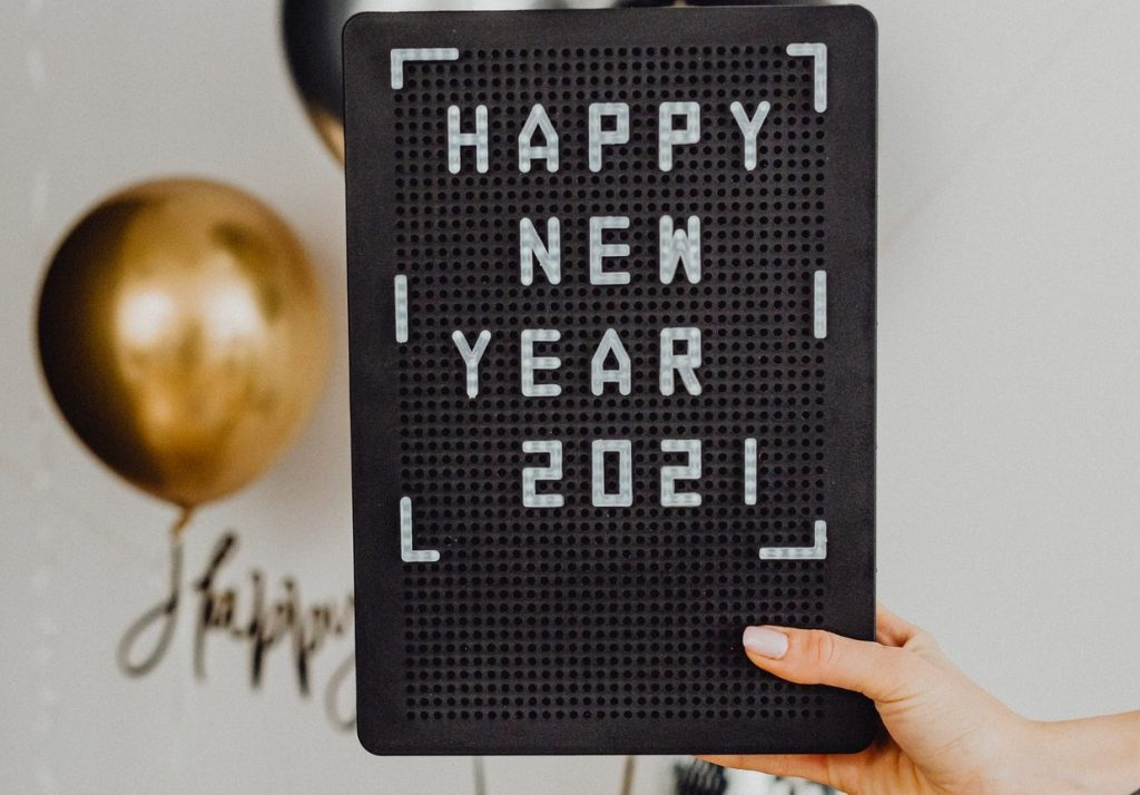 Person Holding A Happy New Year Text On A Black Board | Breast Cancer Car Donations