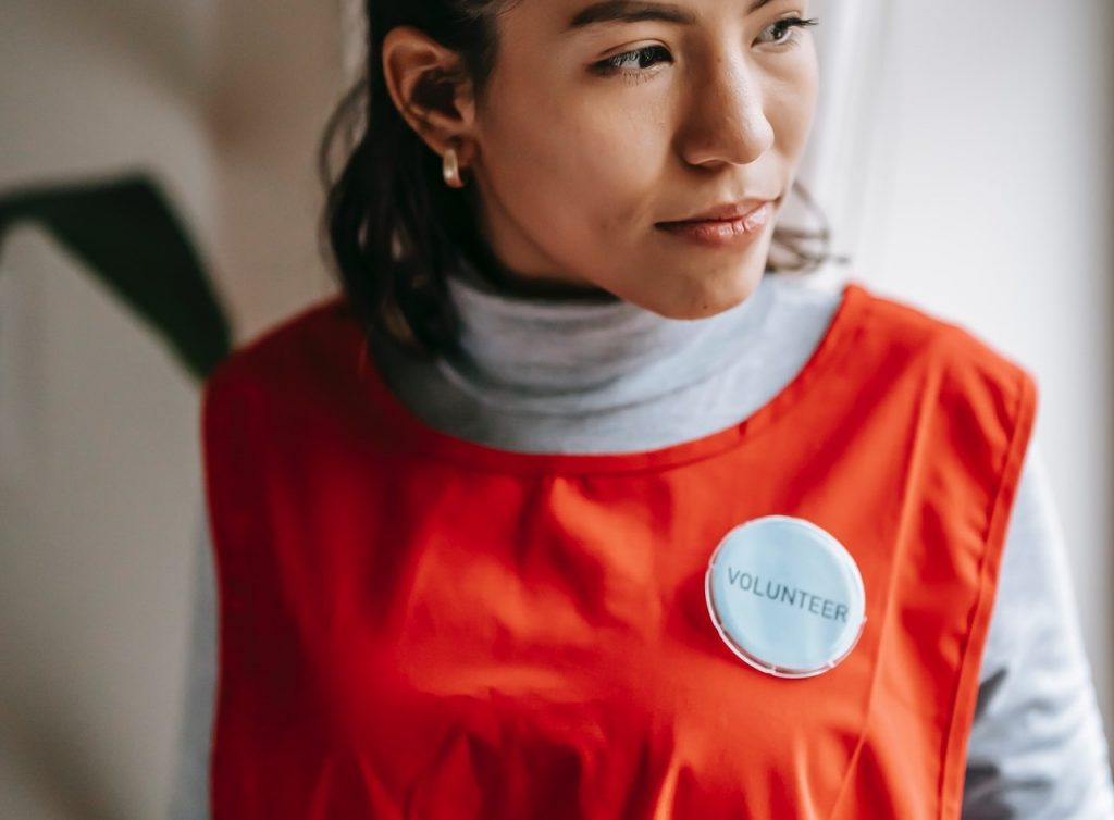 Volunteer in Orange Suit | Breast Cancer Car Donations
