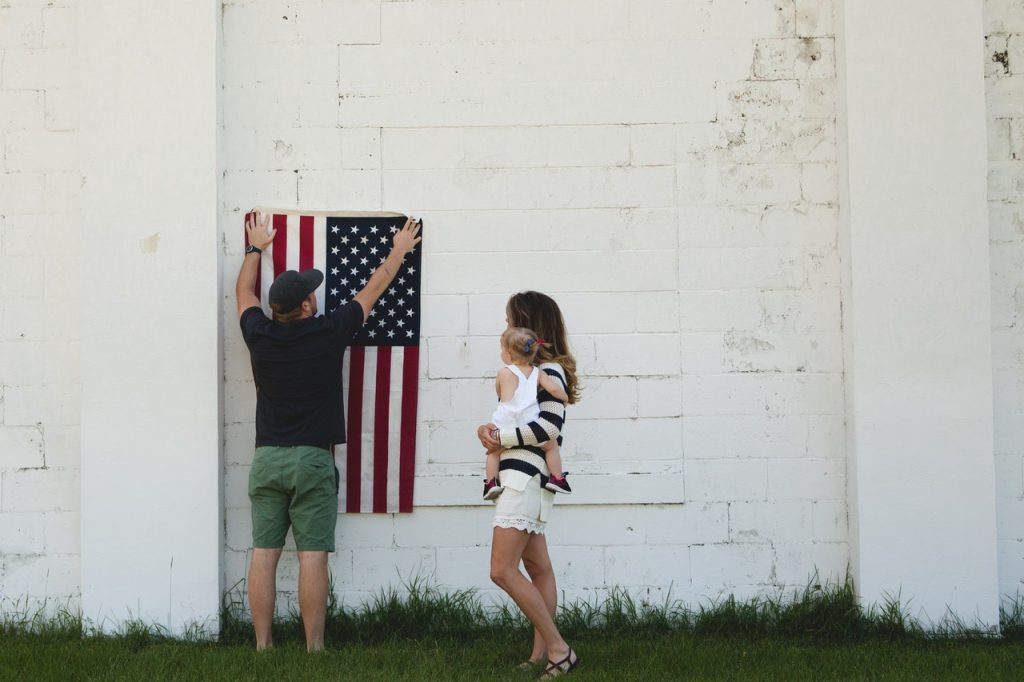 Family Hangs US Flag on a Wall | Breast Cancer Car Donations