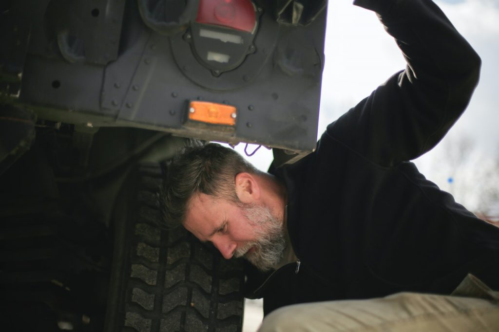 Person Checking Car Tire Pressure | Breast Cancer Car Donations