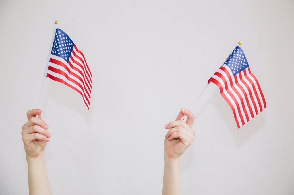 Hands Waving US Flag | Breast Cancer Car Donations