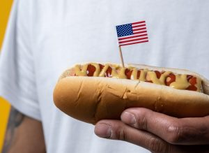 Person Holding a Hotdog with the US Flag   Breast Cancer Car Donations