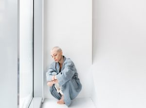 Woman Leaning on a White Wall | Breast Cancer Car Donations
