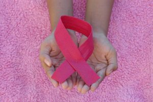 Hand Holding Pink Ribbon For Breast Cancer Awareness   Breast Cancer Car Donations